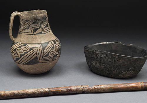Three Chaco Canyon anthropology artifacts— a pitcher, bowl, and walking stick—display different painted patterns.