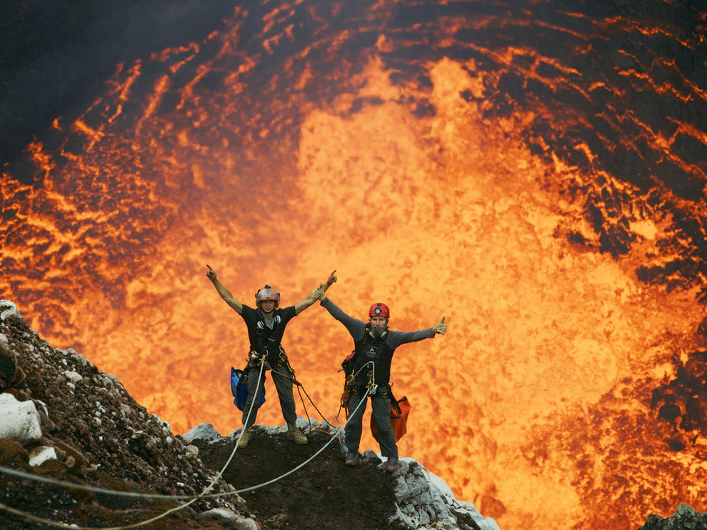 Two men are suspended on ropes above an active volcano crater.