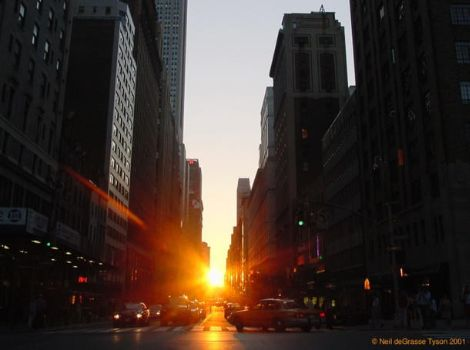 The sun setting on 34th street in New York City, framed by buildings in the twice-annual event known as Manhattanhenge.