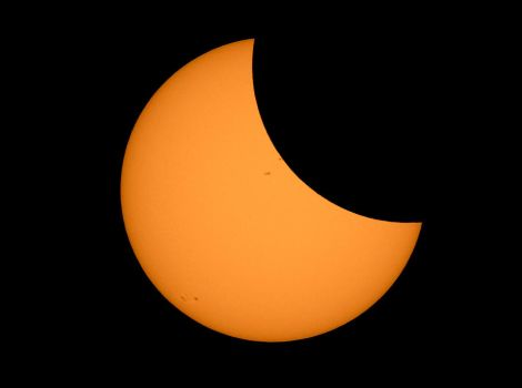 The moon appears as a solid dark shape covering 1/3 of the sun.
