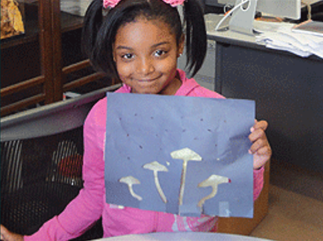 A young child holds up a drawing