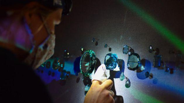 Exhibition staff member polishes gems.