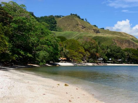 Sandy beach in the foreground, with a view of tree-covered mountains where they meet the sea.