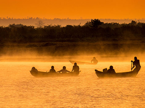 Three boats being paddled down a river in Madagascar are silhouetted against the sunset.