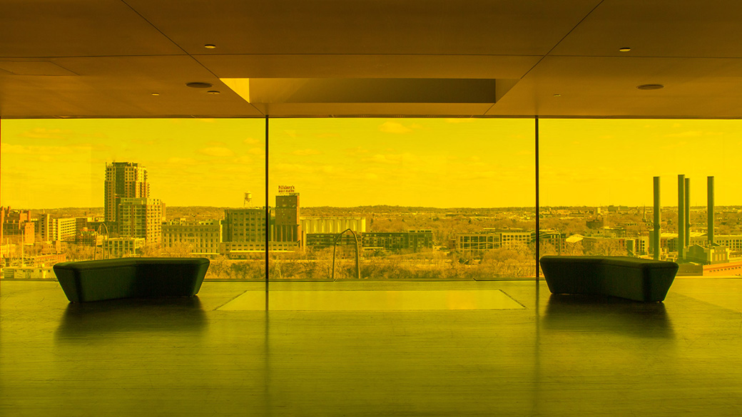 A photo of the amber-hued Dowling Studio lobby, known as the Amber Box. In the foreground, two modern benches stand in silhouette against three floor-to-ceiling windows overlooking the Minneapolis Riverfront skyline.
