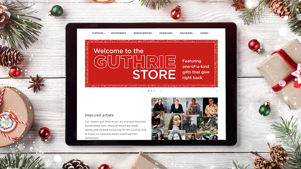 "A top-down view of a white wooden table strewn with holiday decorations, including pinecones, fir branches and wrapped presents. An electronic tablet sits in the middle of the table and showcases the Guthrie Store website home page that reads, ""Welcome to the Guthrie Store, Featuring one-of-a-kind gifts that give right back."""