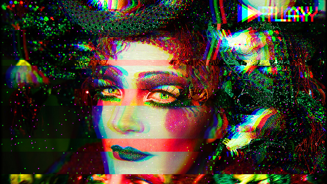 "A holographic portrait of Taylor Mac in brightly colored makeup, including green glitter lipstick, dramatic eye shadow, false eyelashes and a sequined headdress. In the upper right corner, a white, triangle play button is followed by the word ""PLAY,"" similar in style to what you would see when watching a VHS tape"