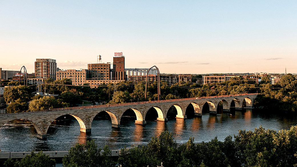 A sunset view of the Stone Arch Bridge and Mississippi River as seen from the Guthrie's Endless Bridge.