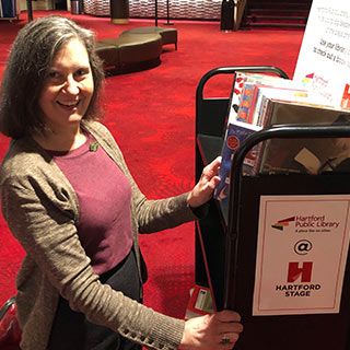 Elizabeth Davis, Head of Circulation and Access Services for Hartford Public Library, stocks books for the library branch kiosk at Hartford Stage for 'Jane Eyre'