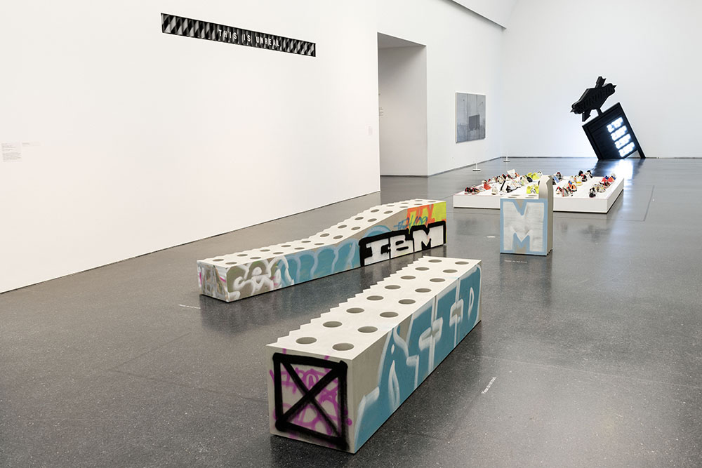 A white room with concrete benches that have graffiti on them.