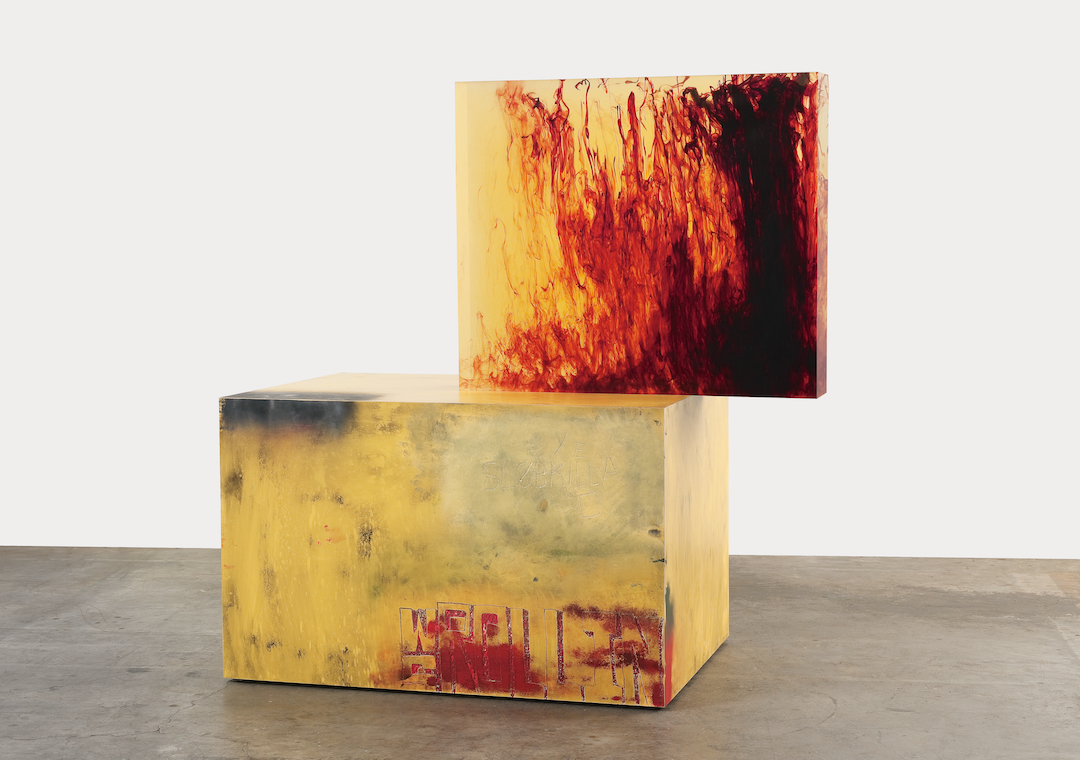 A red and orange sculpture made from two cubes stacked on the gallery floor.