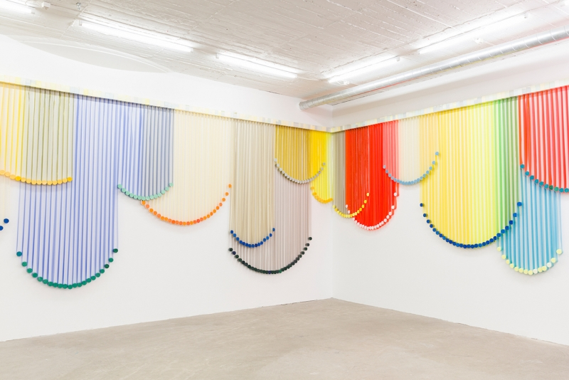 A hanging wall sculpture made from overlapping colorful strips.