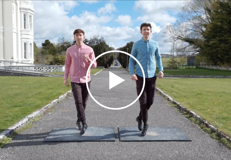 Two men wearing Irish step shoes, mid-step on tap boards in the middle of lane. Play button in middle of image.