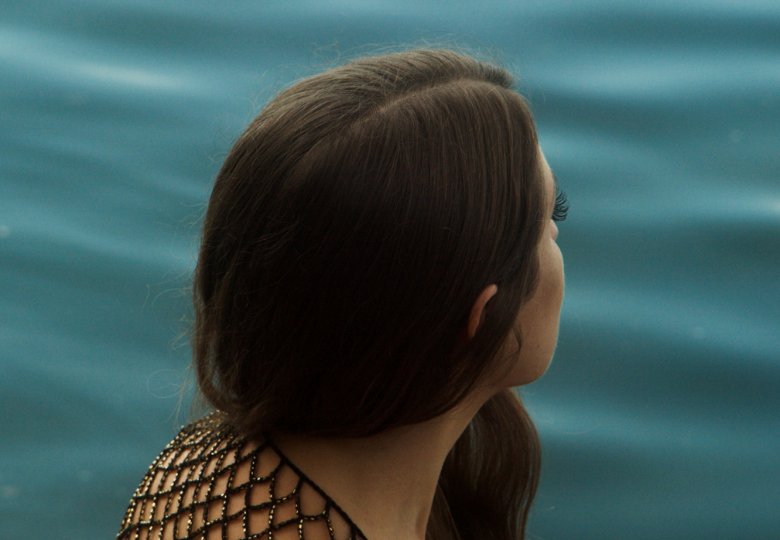 A woman turned away from the camera, looking at a body of water
