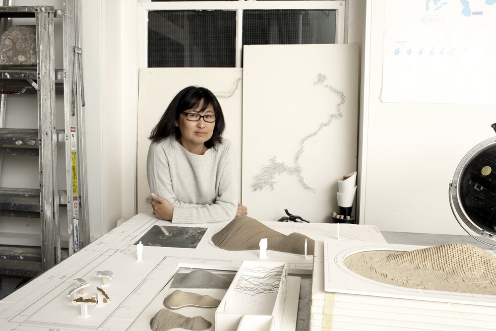 Maya Lin sitting at a table in her studio. On the table in front of her are models of her earthworks.