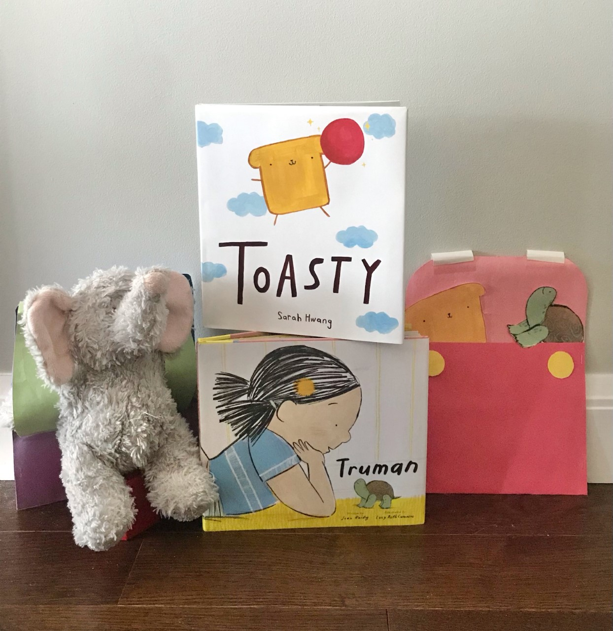 """A fuzzy stuffed elephant toy, the books """"Toasty"""" and """"Truman"""" stacked on top of each other, and a backpack made of paper."""