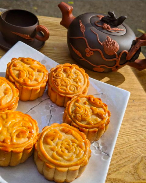 A plate of round mooncakes, a small brown teapot, and teacups.