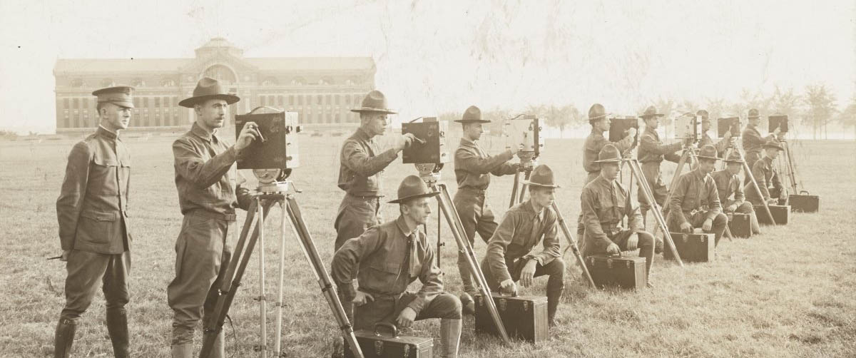 Line of WWI soldiers in uniform operating cameras, likely in training