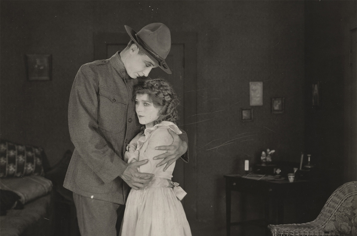 Movie still, with young woman (Mary Pickford) being embraced by man in WWI uniform.