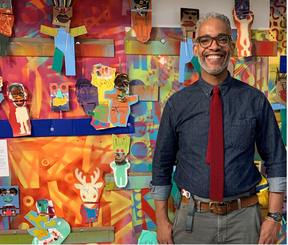 Anwar Floyd-Pruitt posing in front of artwork