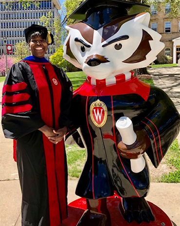 Dawn Crim standing with a Bucky statue