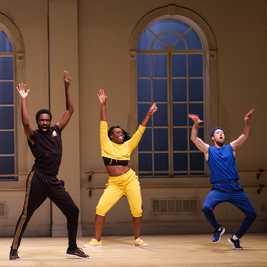 Three actors dancing gleefully with their arms in the air and expressive joyful faces.