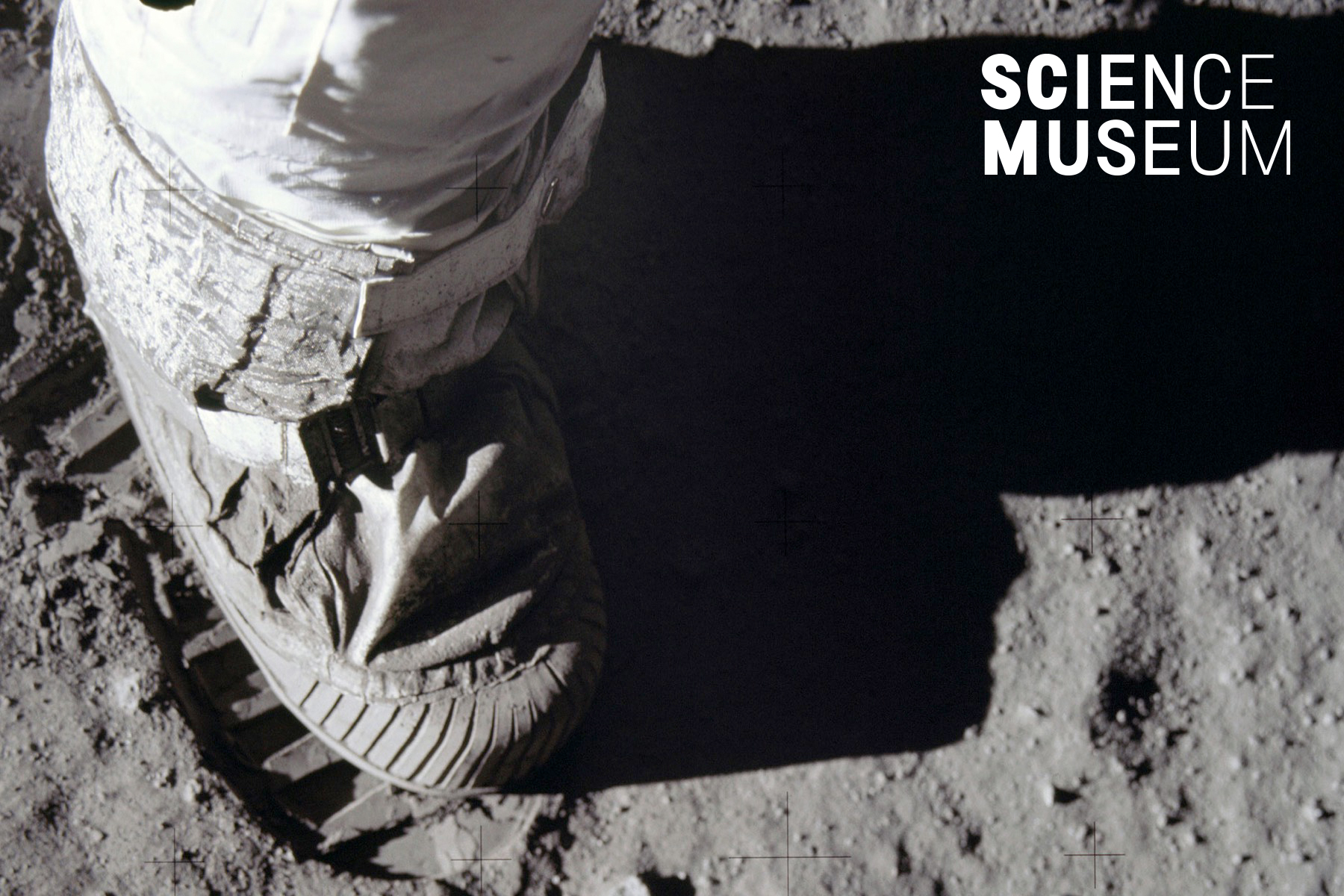 Black and white photograph of a foot in a spacesuit making a footprint on the surface of the Moon (NASA)