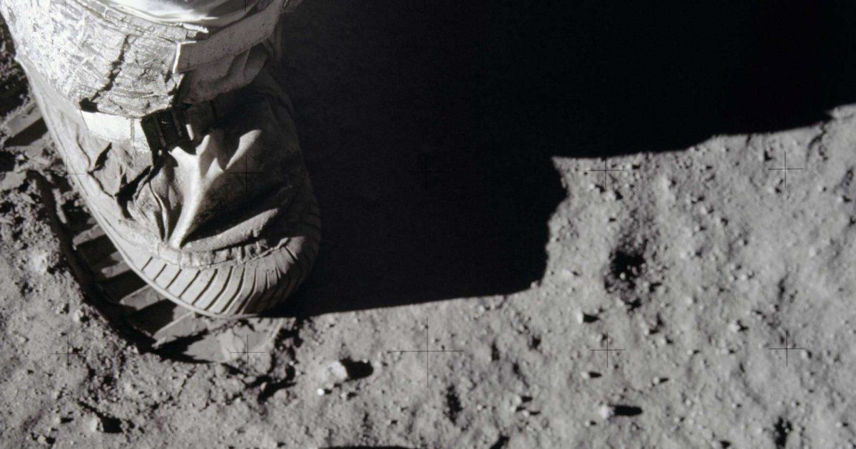 Black and white photo of a space boot on the surface of the moon.