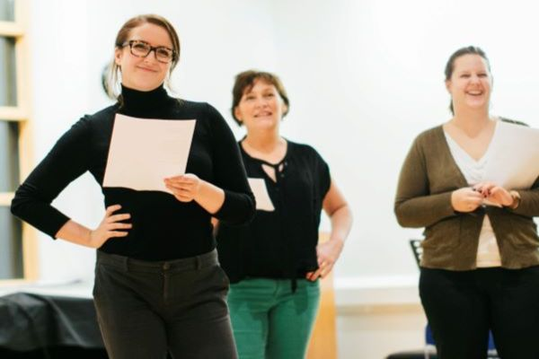 [IMAGE] Three teachers participating in a CPD workshop holding scripts