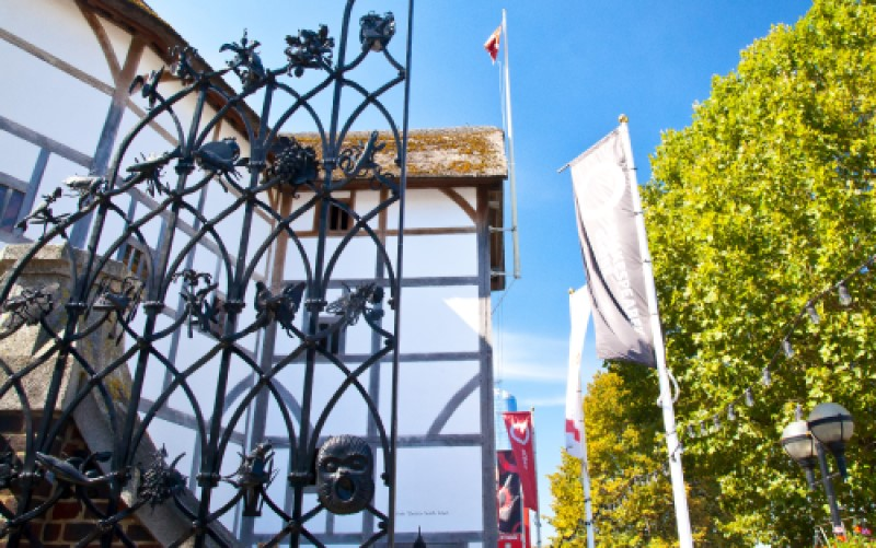 [IMAGE] A view of the Globe Theatre through the iron work of the Groundling Gates on a sunny day.