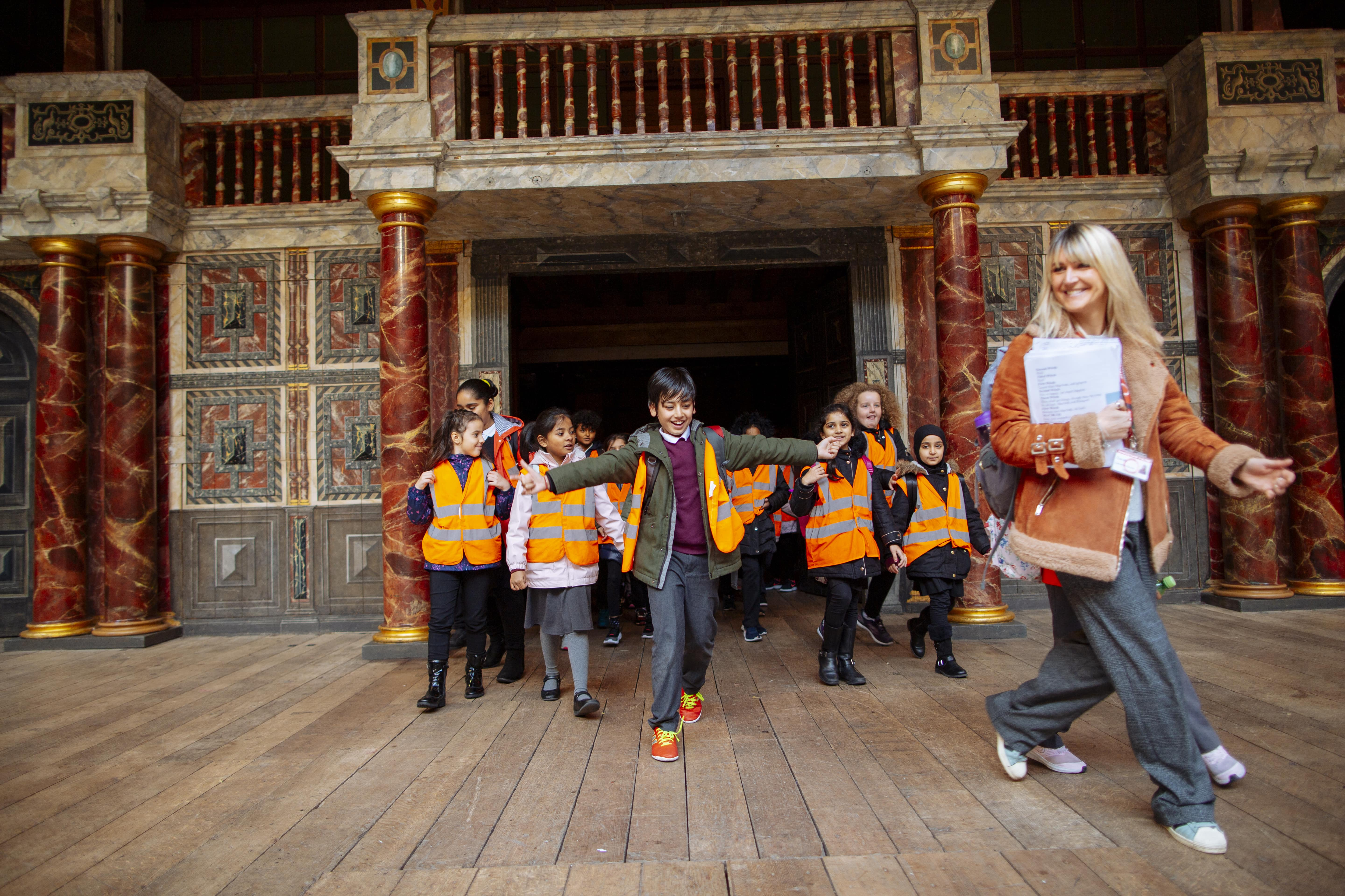 [IMAGE] Photograph of excited primary school pupils in a Lively Action workshop, on the guided tour of the Globe, coming through the mainstage doors onto the stage with their workshop leader