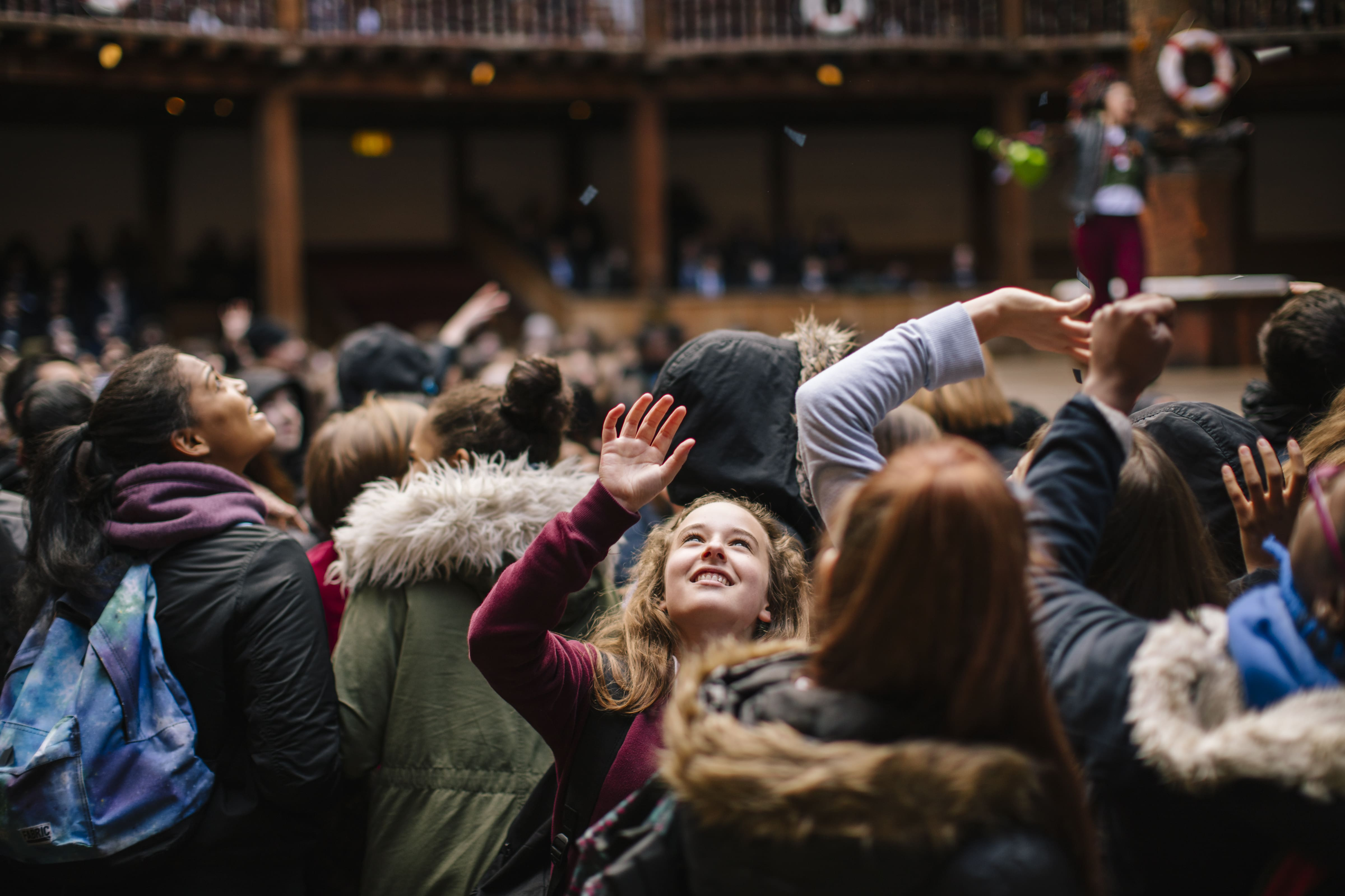 [IMAGE] Audience of children/young adults in school uniforms watching a Playing Shakespeare with Deutsche Bank performance from the Yard, confetti is falling, they are looking up and smiling, one girl in particular is slightly facing the camera and smiling whilst reaching up to the confetti