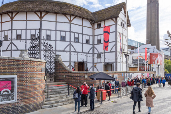 [IMAGE] Photograph by Pete Le May of the Globe Theatre from the outside, showing the the theatre, and audience members awaiting entry whilst following new social distancing rules and covid safety procedure