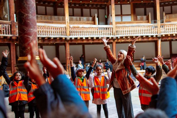 [IMAGE] A group of schoolchildren and a facilitator with their hands in the air.