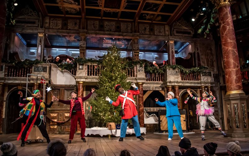 [IMAGE] The cast of Christmas at the (snow) Globe wave their hands in the air on the globe stage with a huge Christmas tree behind them.
