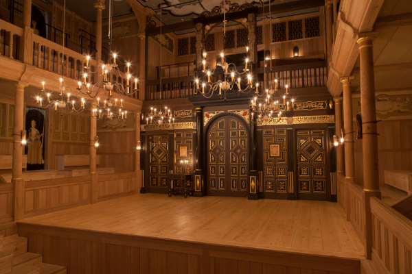 [IMAGE] The interior of the Sam Wanamaker Playhouse: an empty wooden, ornate stage with candelabra hanging above it.