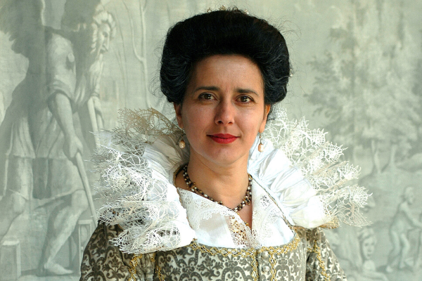 [IMAGE] Actor Yolanda Vazquez is wearing an ornate Elizabethan ruff and gown. Her dark hair is up in a big bun.