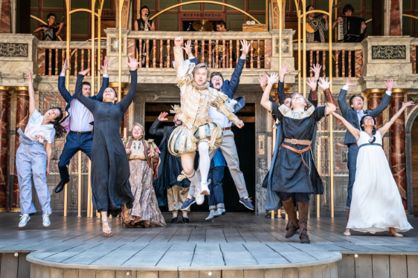 [IMAGE] A company of actors on the Globe stage. They're all jumping up joyously, their arms in the air.