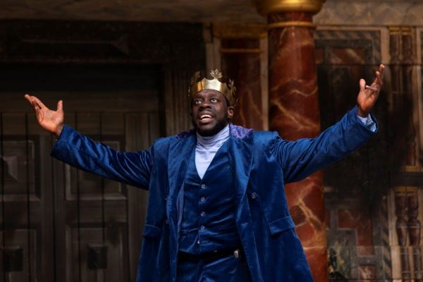 [IMAGE] A man in a blue velvet suit wearing a crown and has his hands up