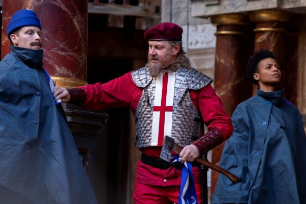 [IMAGE] A scene from a play in which a man is holding an axe and has two guards on either side.