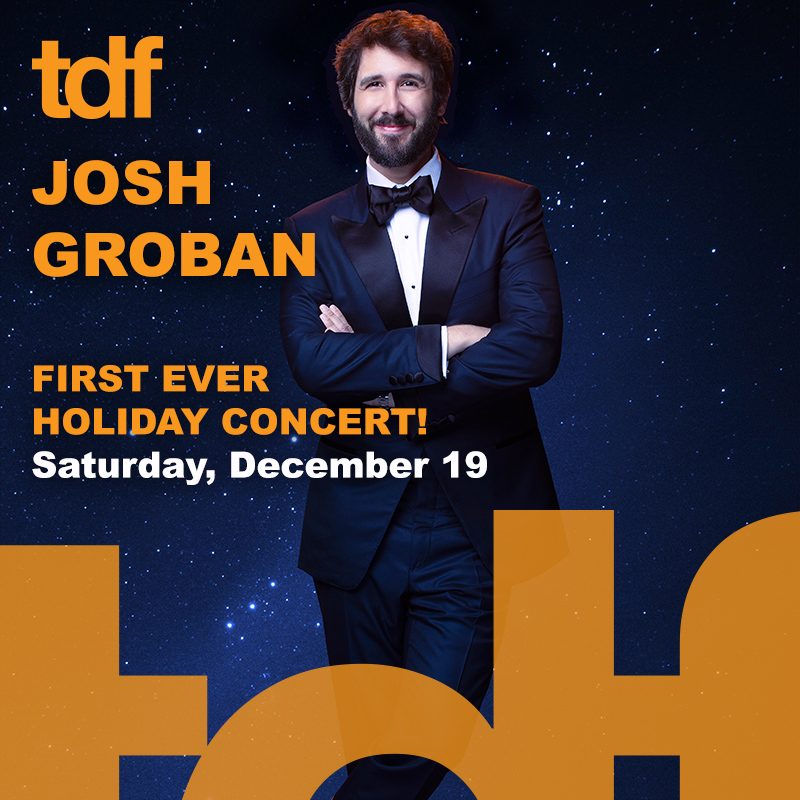 Photo of Josh Groban wearing a dark blue suit, white collared shirt and bowtie. He is smiling with his arms crossed around his chest. Text: JOSH GROBAN First Ever Holiday Concert Saturday, December 19