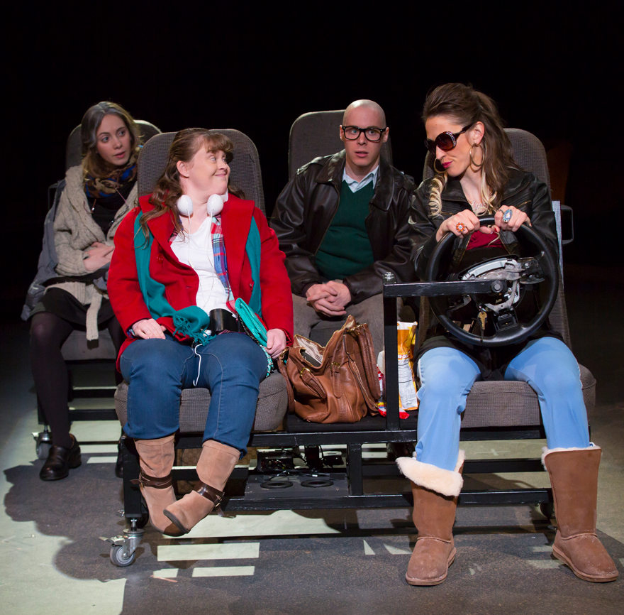 four white actors in coats simulating driving and riding in a car on stage.