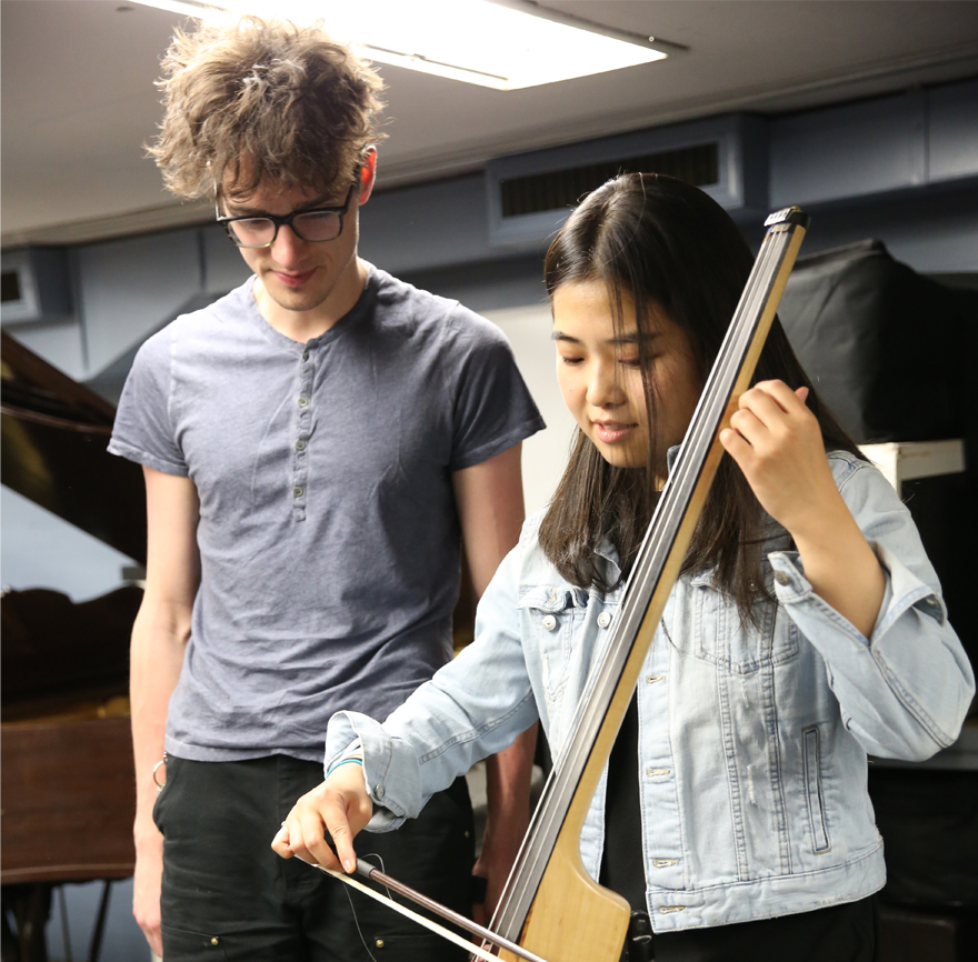 a young woman playing a tall stringed instrument while a young man observes