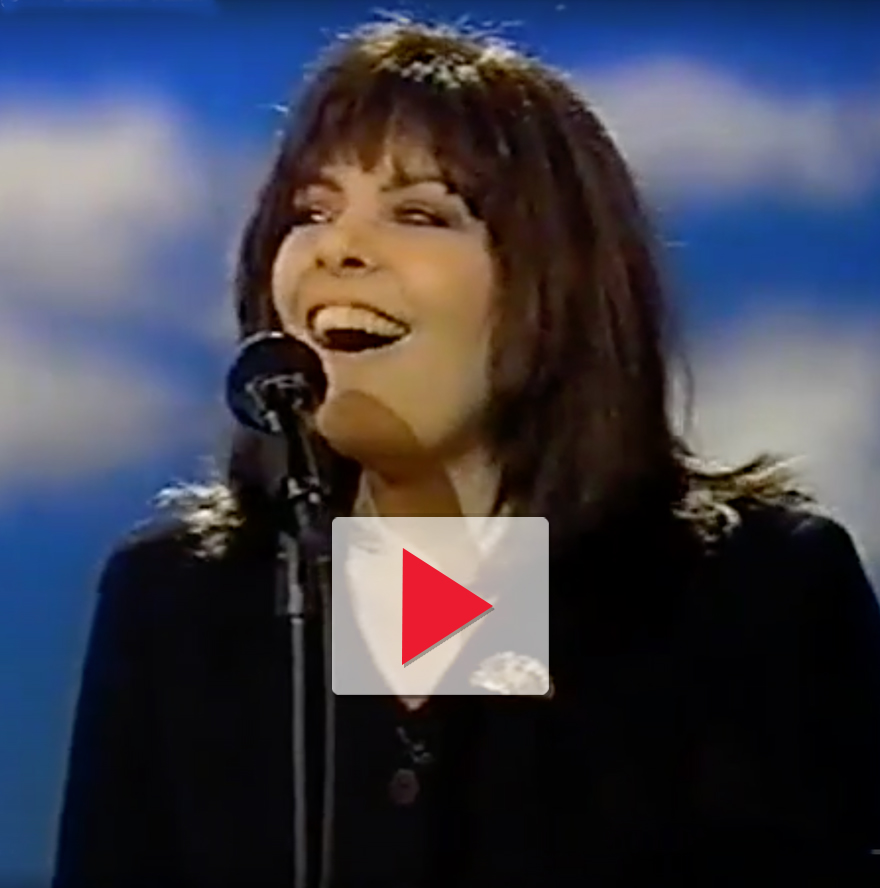 a still of a woman singing and smiling