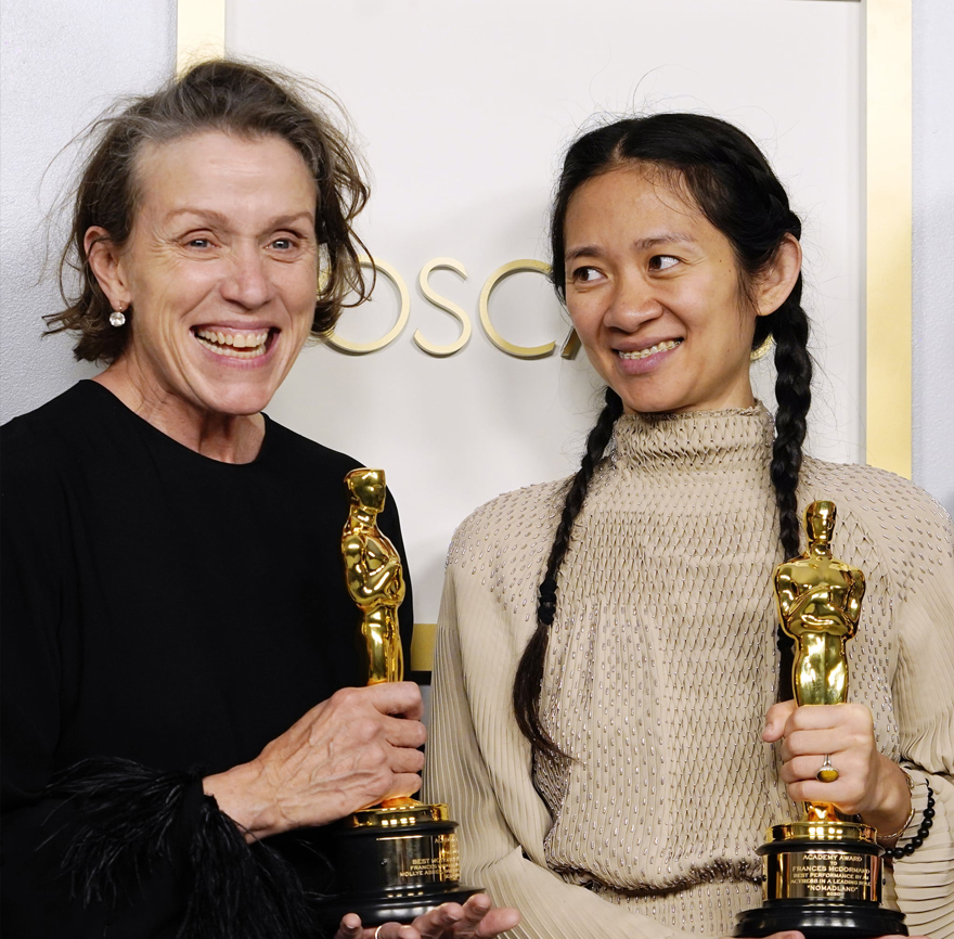 two smiling women holding Academy Awards