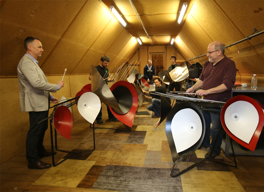 several men playing large percussion instruments in a small room